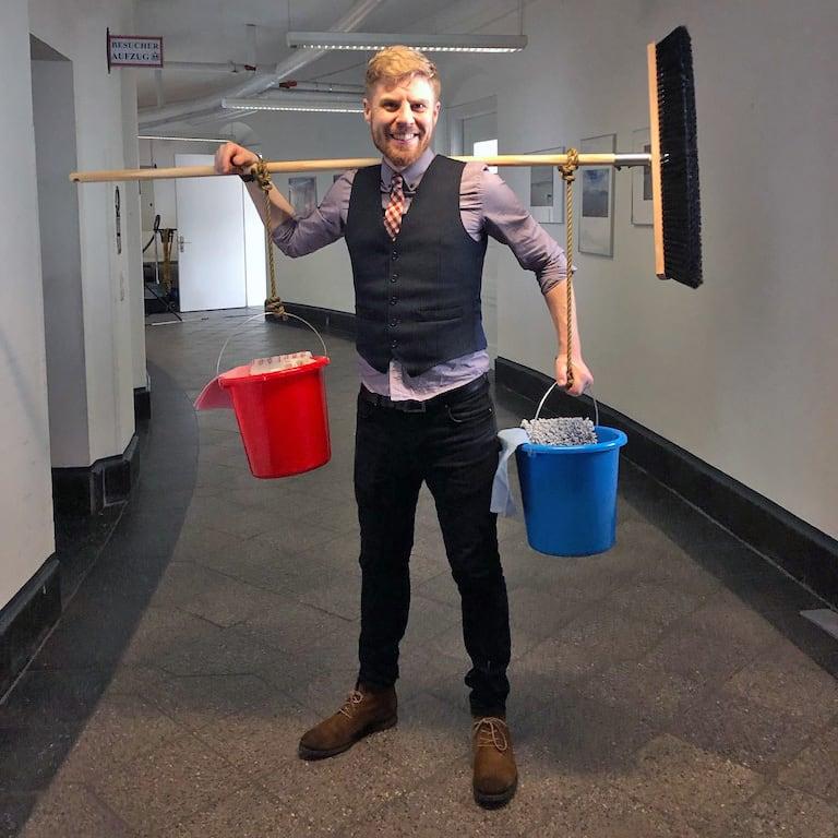 Fotograf Julian-Keno Lilienthal posiert mit dem Wasserträger-Geschirr